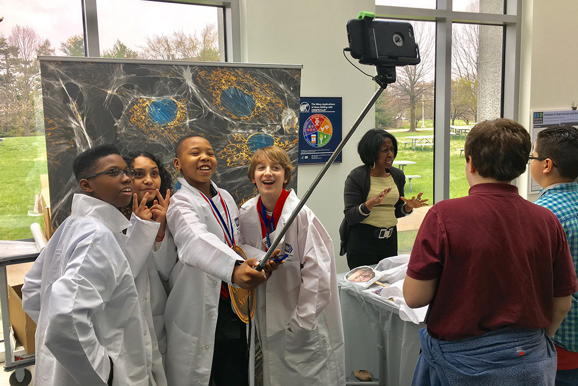 Students wearing lab coats take a selfie