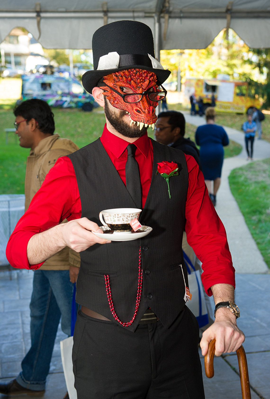 An NIH'er dressed in red and black and monster mask leans on a cane, holds a cup of tea