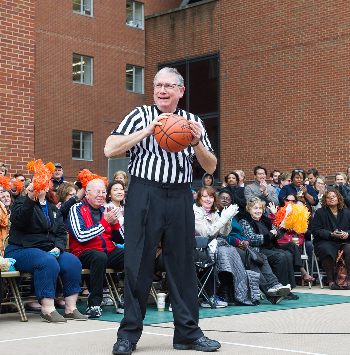 A smiling Tabak stands with basketball in front of crowd.