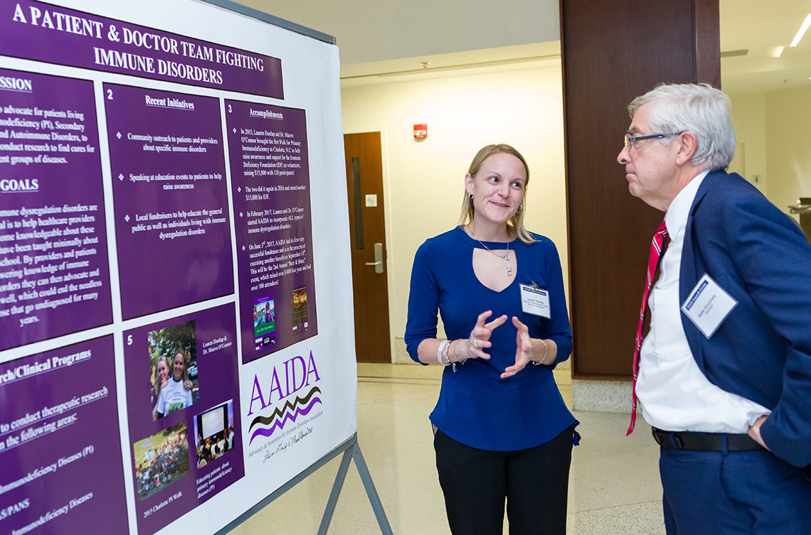 Dunlap stands with Dr. Koroshetz in front of poster with purple panels describing the fight against immune disorders