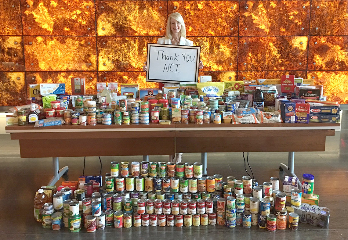 Siegle holds thank you sign behind long table filled with canned goods