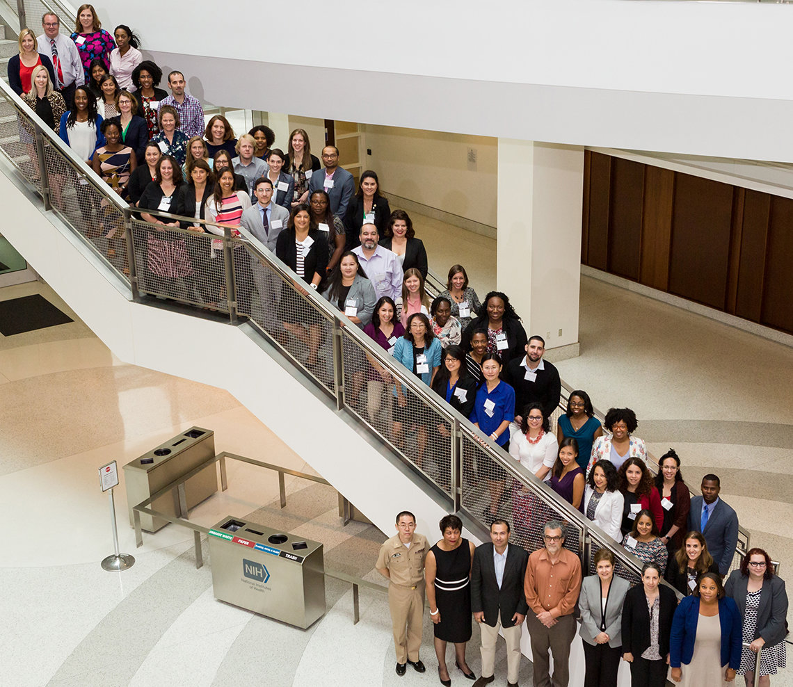 Dozens of NIMHD research scholars pose for photo along a staircase.