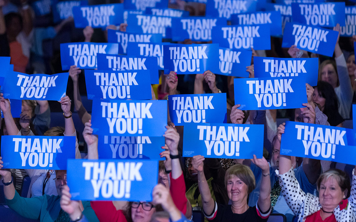 """People in crowd hold high blue signs that read, """"thank you"""""""