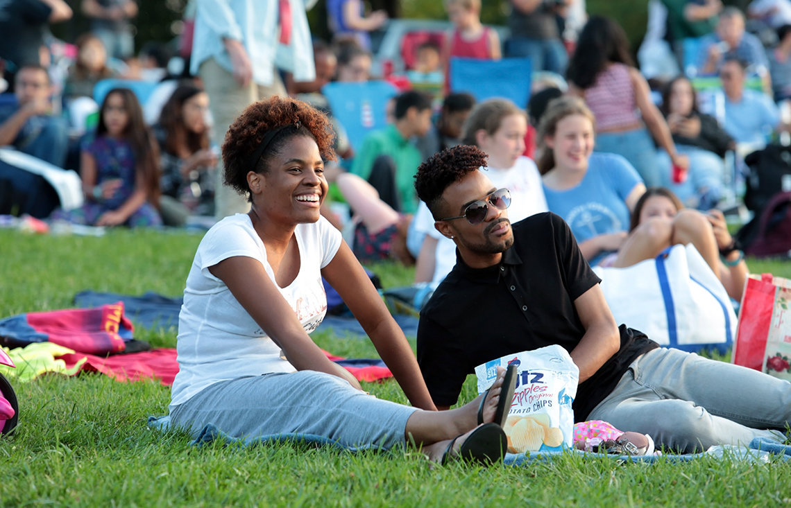 Two NIH'ers relax on the lawn with a bag of potato chips.