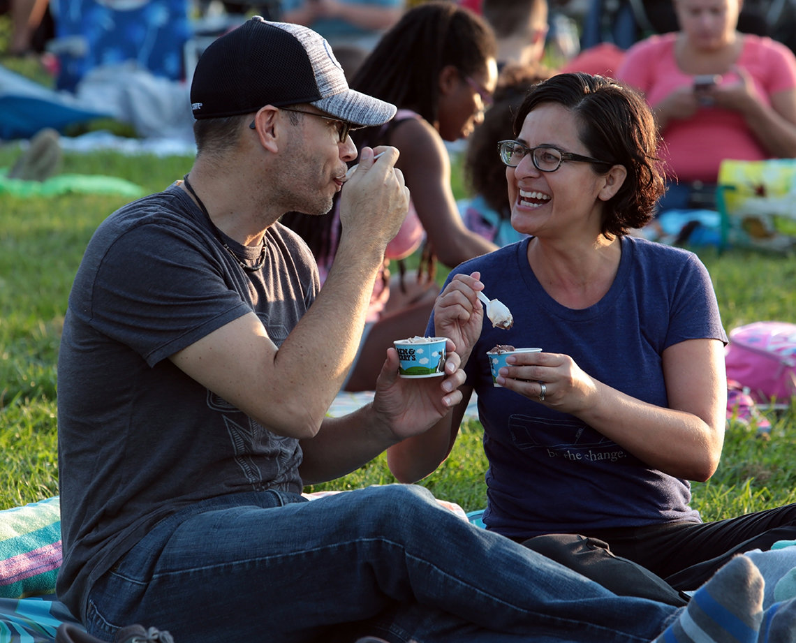 A smiling couple enjoys ice cream on the lawn.