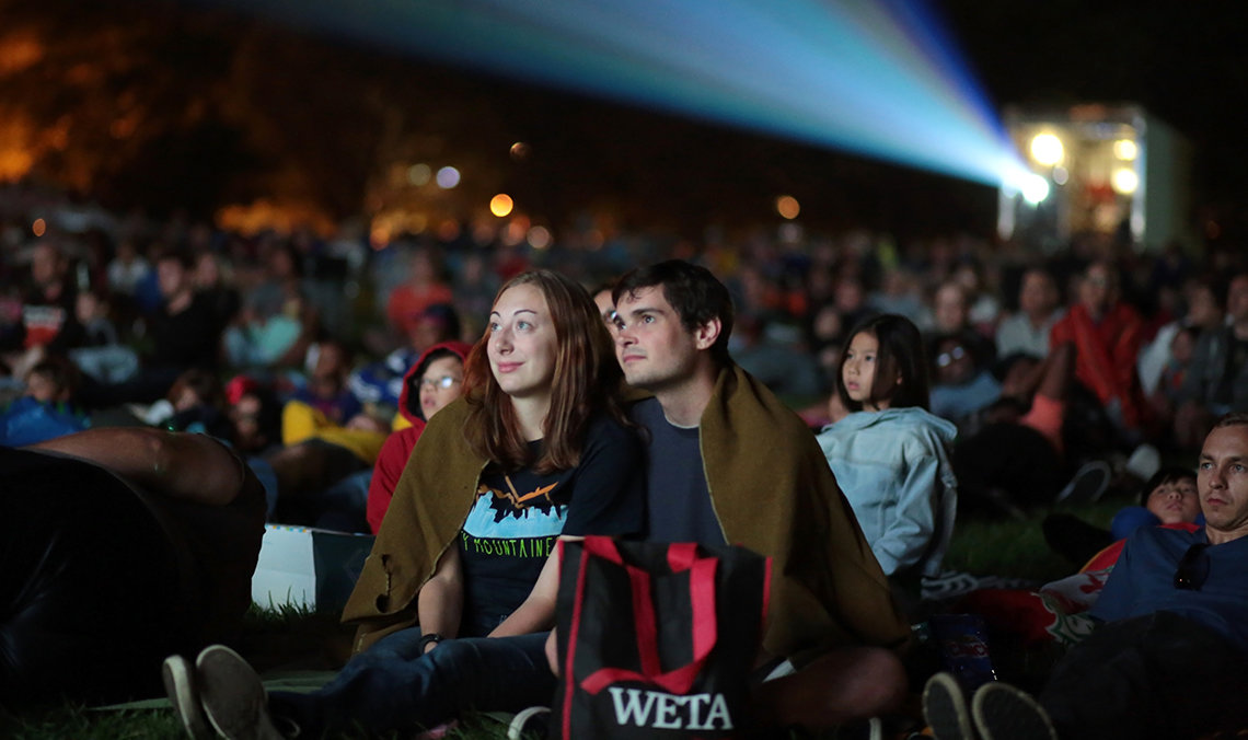 A young couple wrapped in a blanket watches the movie that began after sunset.