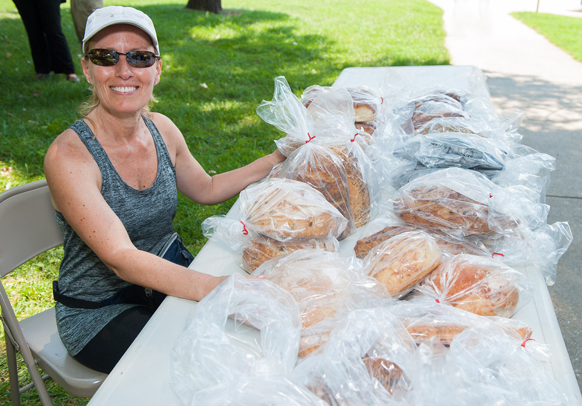 The smiling bread lady sits at table with loaves for sale at outdoor community market.