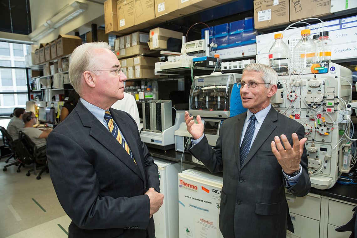Fauci speaks with Price in a lab