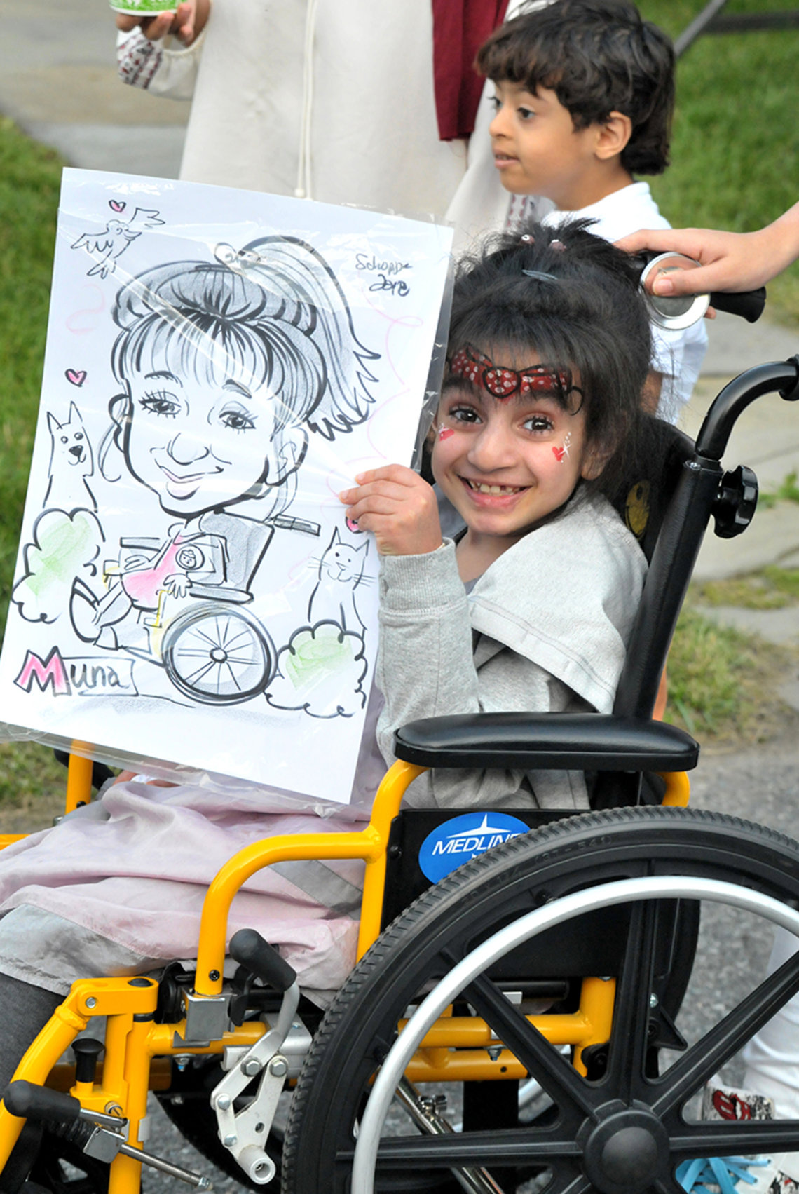 Muna Albusaidi, 8, beams as she shows off the caricature of her made at the inn's summer carnival.