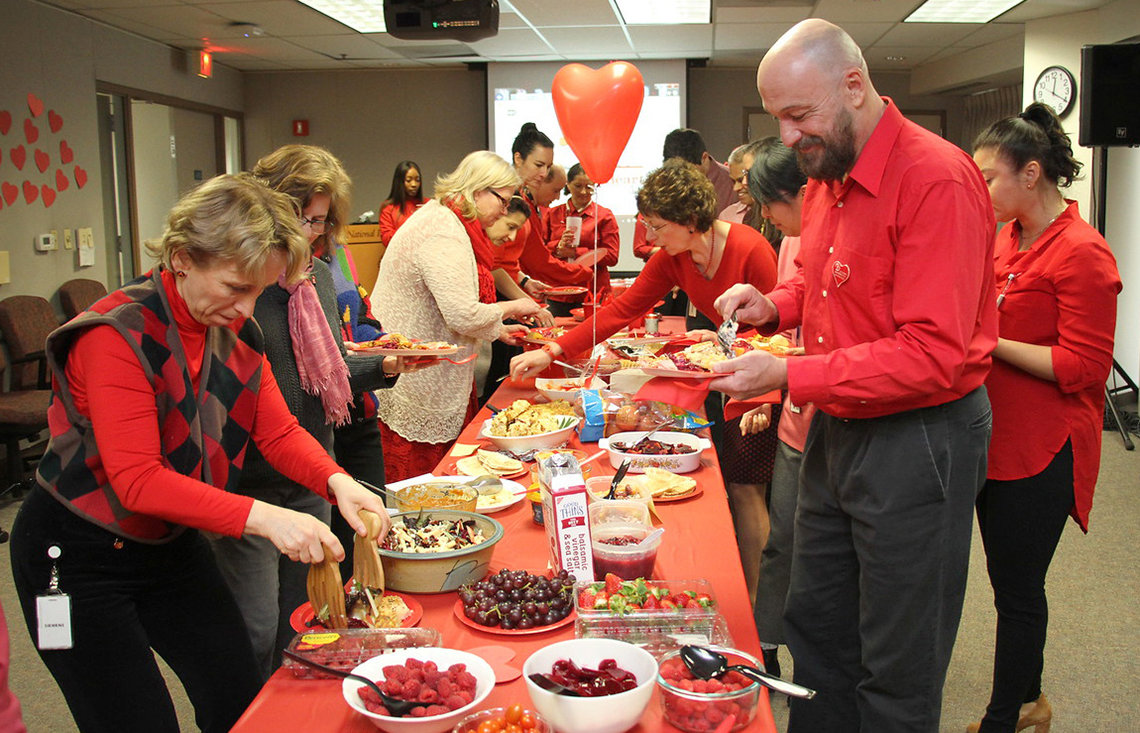 NHLBI staff enjoy a spread of red-colored foods at potluck lunch