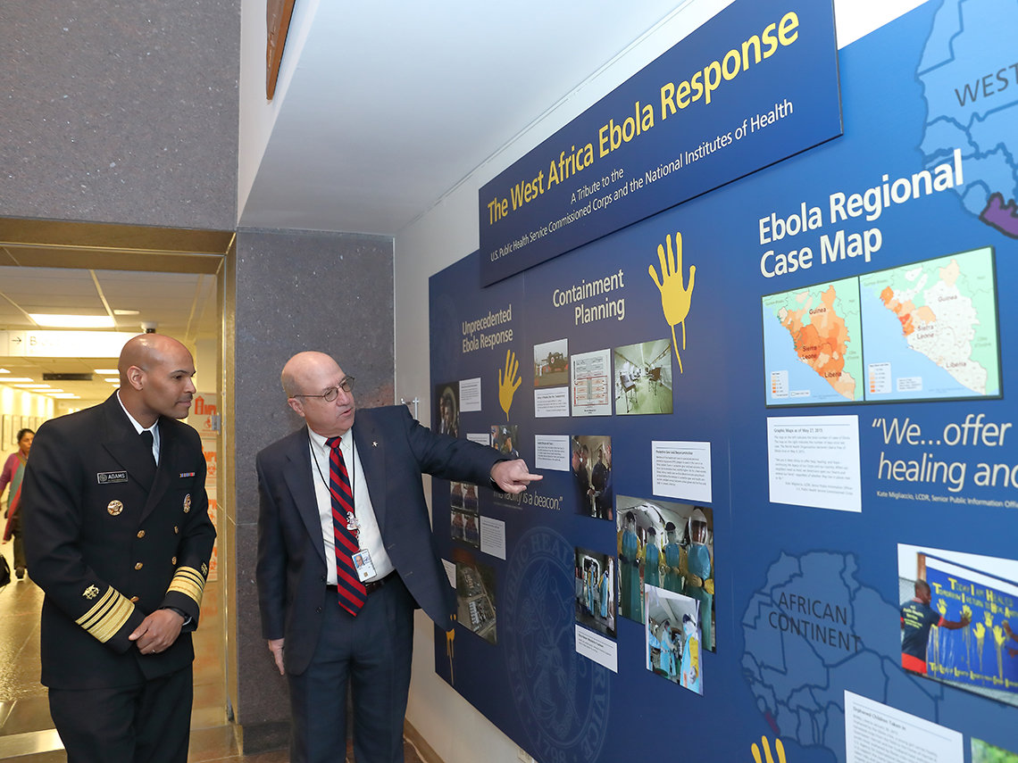 Adams and Gilman look at Clinical Center exhibit on Ebola