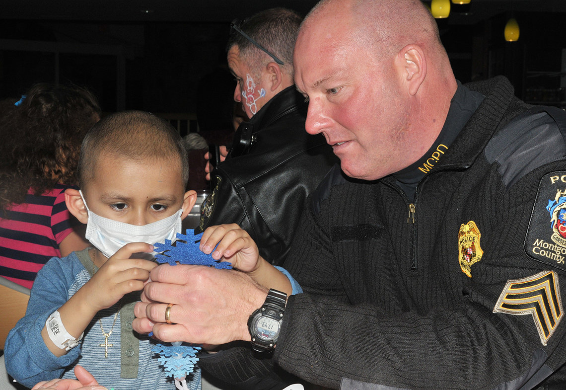 A police officer visits with Children's Inn patient.