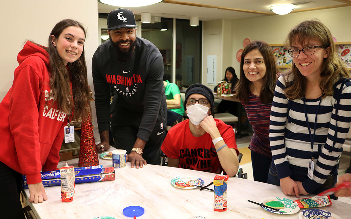 Basketball star decorates cookies at the Children's Inn.