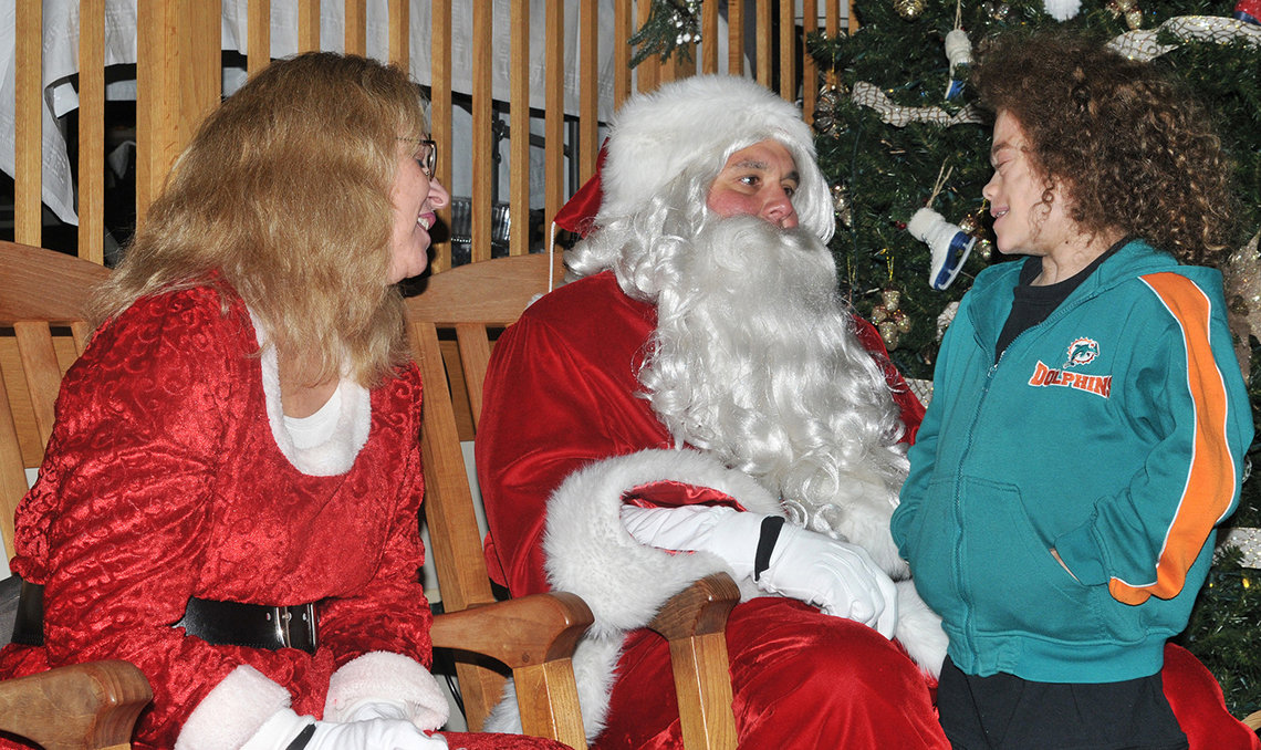 Santa and Mrs. Claus visit with an inn patient.