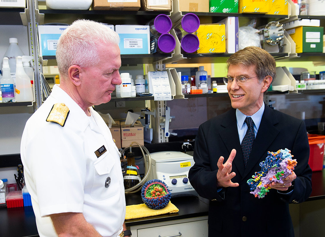 Boyington shows Dr. Fauci details of a flu virus model.