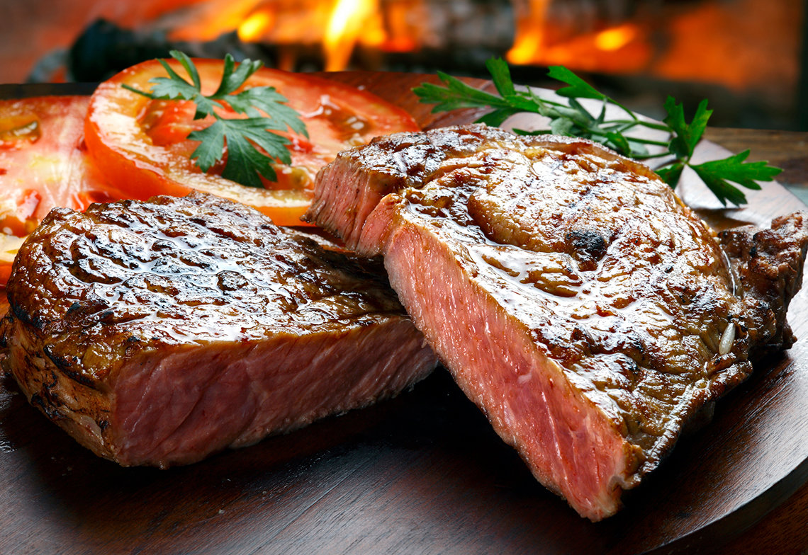 Grilled steak in front of a wood-burning fire.