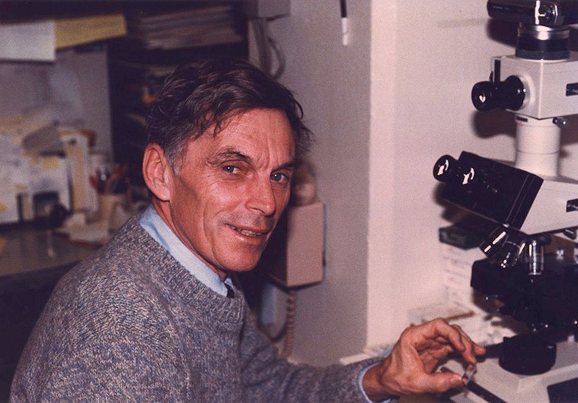 Dr. Michael Potter poses with a tumor sample at a microscope.
