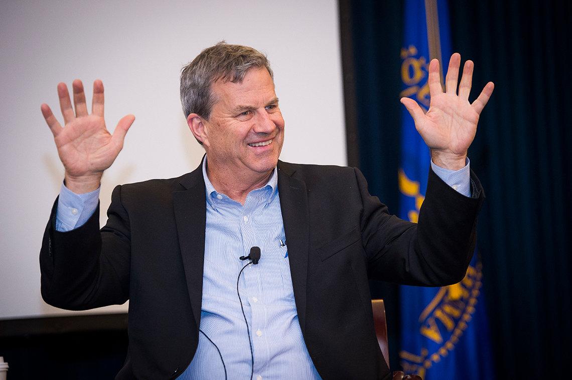 Quinones speaking with his hands raised.