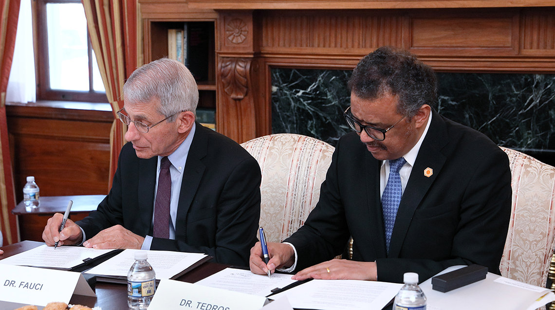 Tedros and NIAID director Dr. Anthony Fauci sign the document.