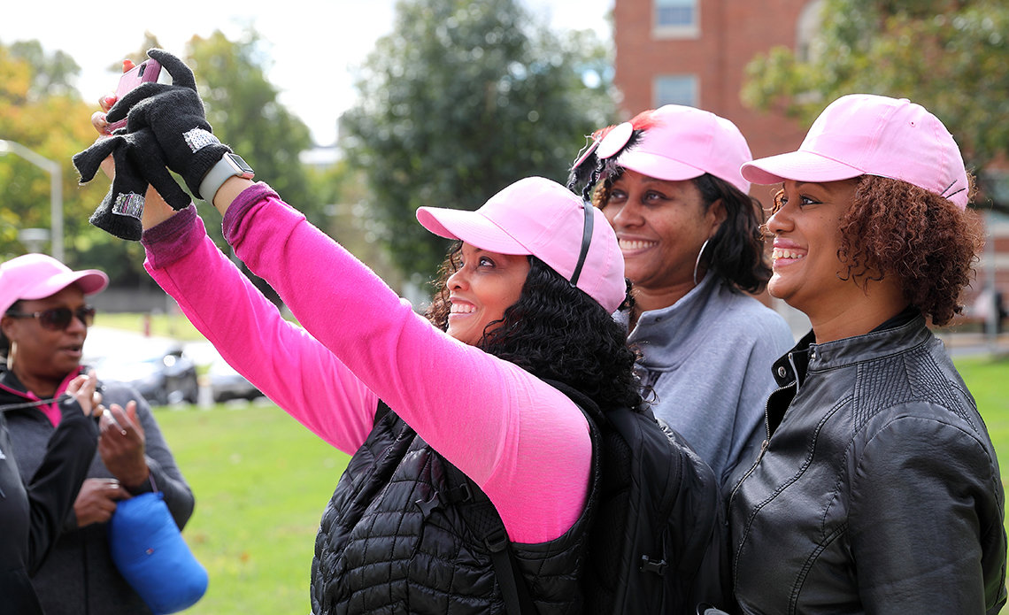 Ladies dressed in pink holding up camera to take a selfie.