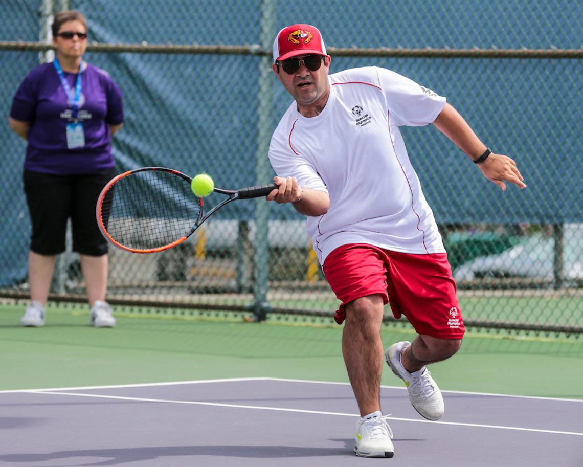NLM's Bijan Bagheri hits tennis ball with his racket.