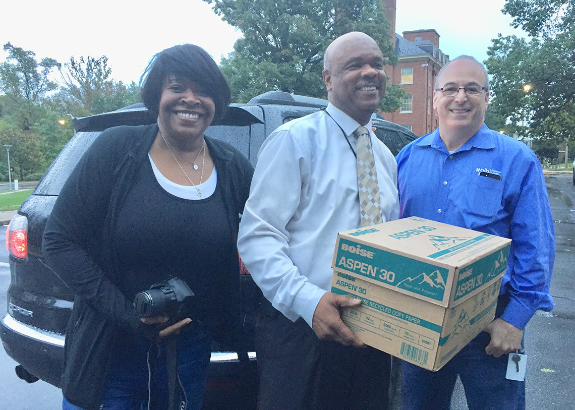 Dr. Johhson carries box of papers to shred with NIHFCU's Hairston and Levin by his side