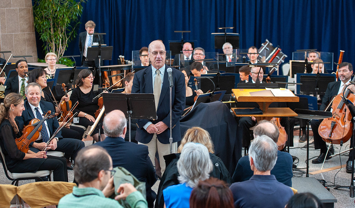 Dr. James Gilman welcomes patients, staff and guests to the NSO performance.