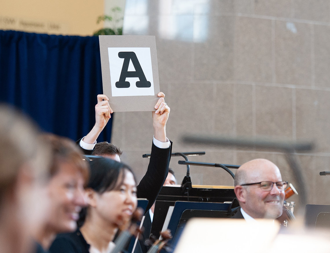 "An orchestra member holds up a sign with a large letter ""A."""