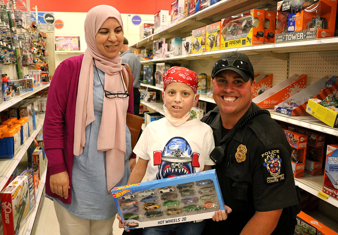 Houssam Merehb and his mom pose with Officer Andrew Martinez while shopping for gifts.