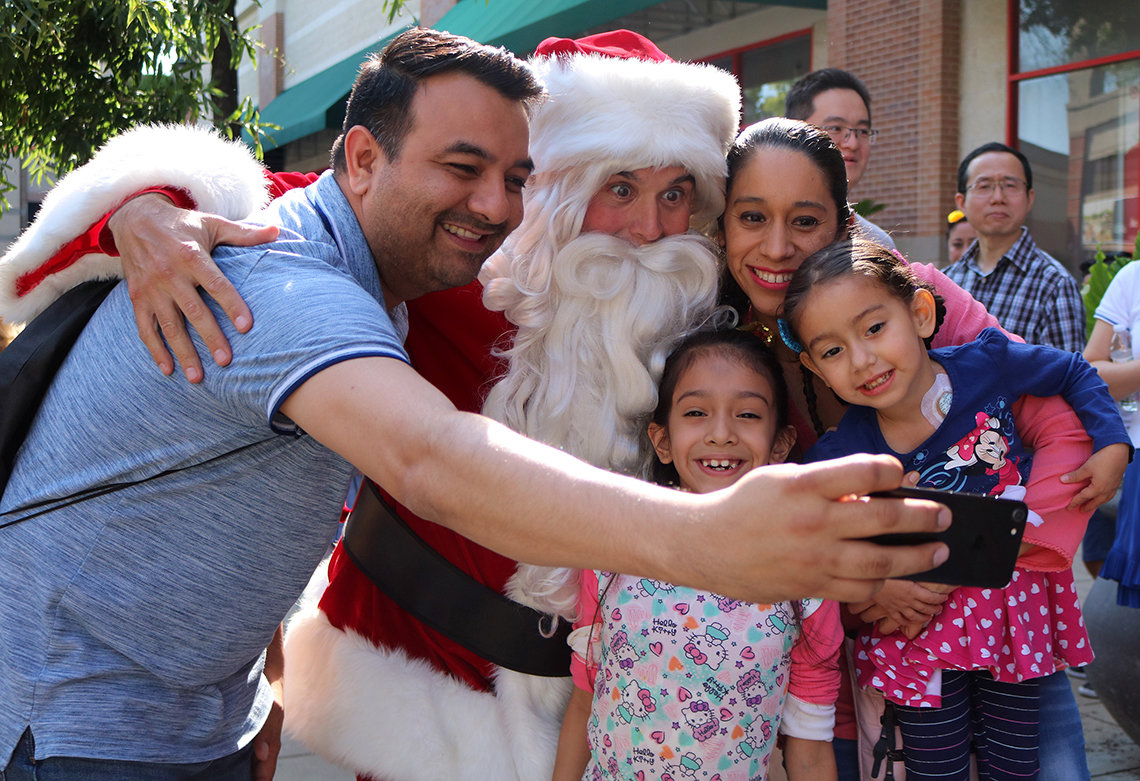 Daniel Beltran and Yury Plata Martinez and their daughters take a selfie with Santa.