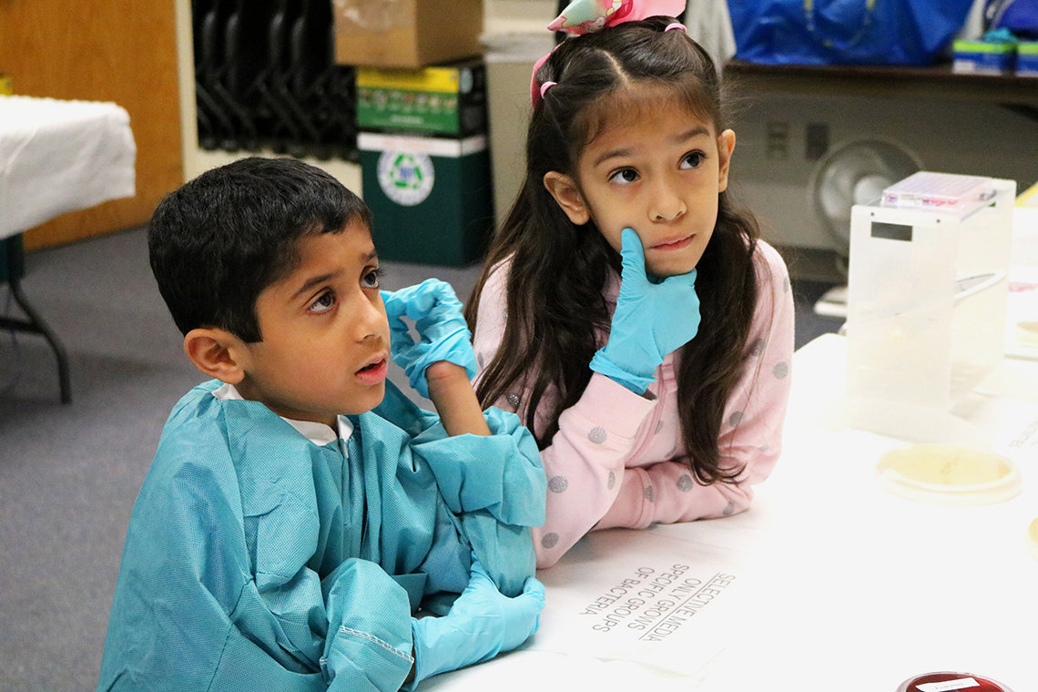 Two siblings of children being treated at NIH listen attentively while seated at at table.