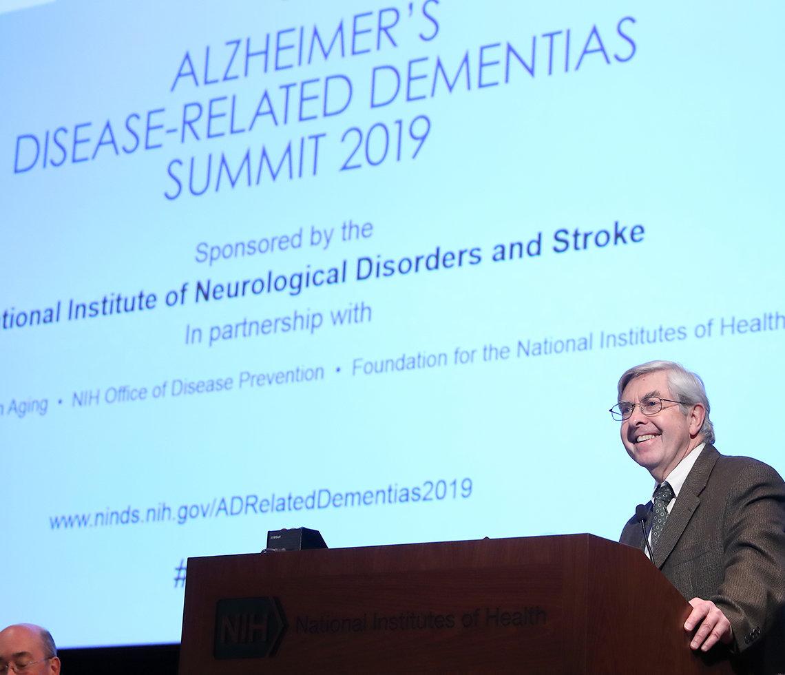 Dr. Koroshetz speaks in front of a screen.