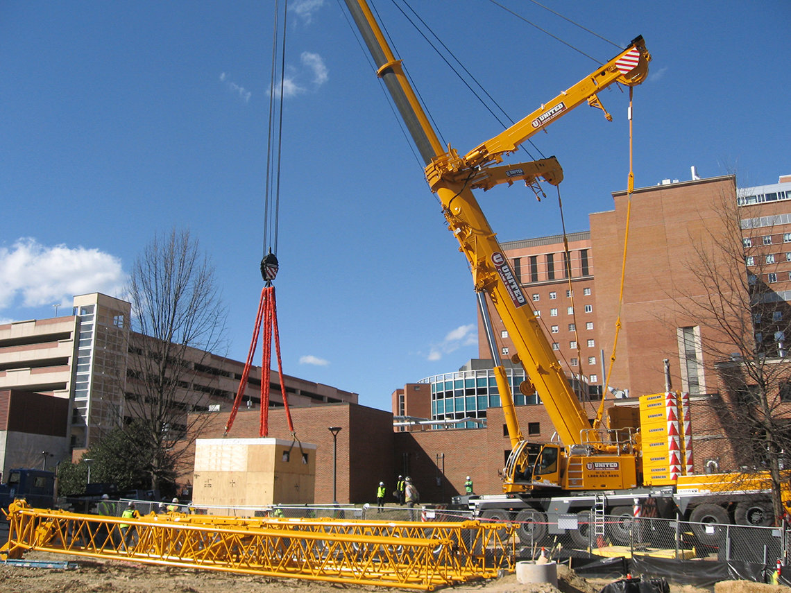 A crane lifts a large box containing a magnet