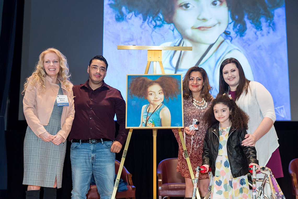 Weltin, surrounded by Amber's family and Feinberg, presents a painting featuring Amber to the rare patient art collection