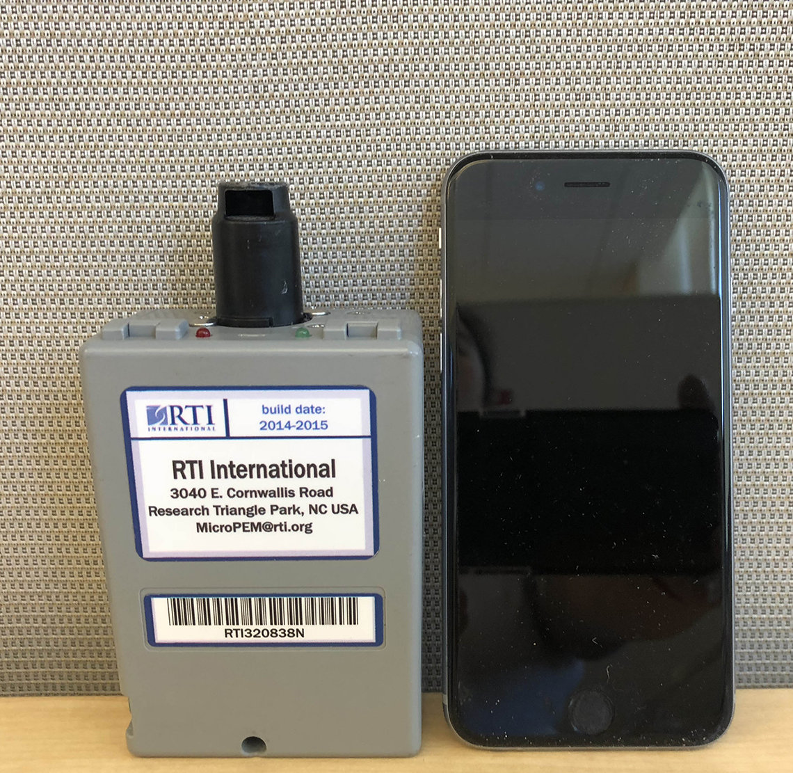 The device sits to the left of a cell phone