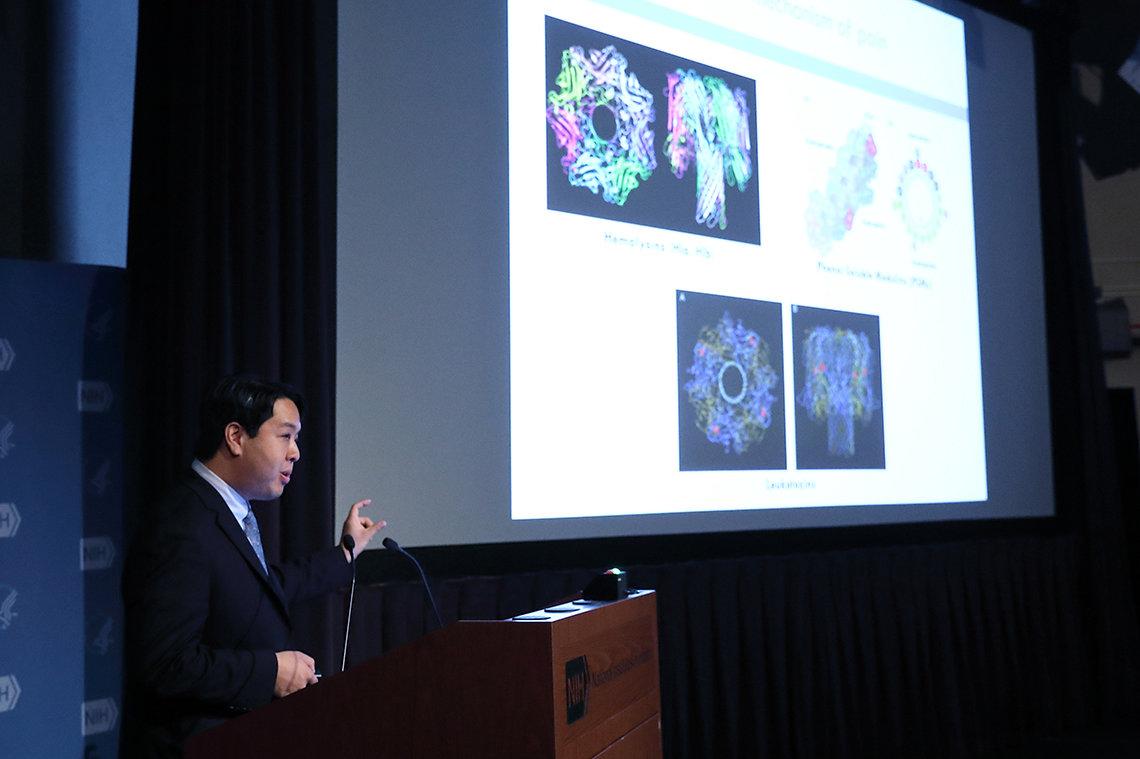 Dr. Chiu stands next to slides