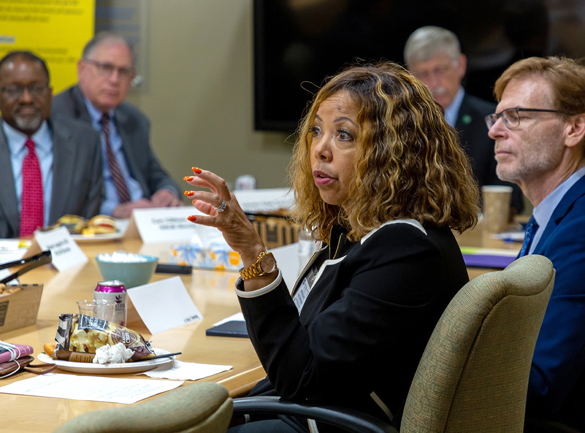 Rep. Lucy McBath (GA) speaks to NIH leadership seated around a conference table,