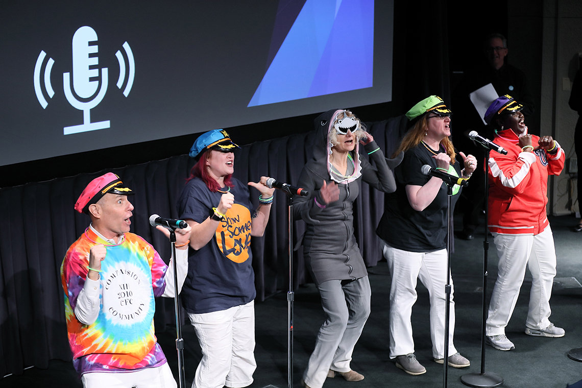 Five people, four wearing ship captain's hats and one wearing a shark costume, sing on stage.