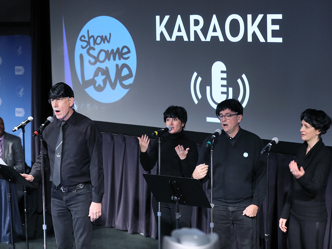 Four people wearing black Beatles'style wigs sing on stage