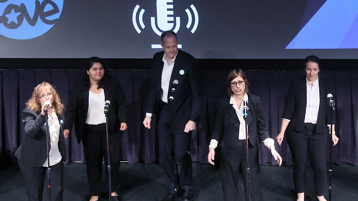 Five people wearing black suits with white shirts sing at the microphones