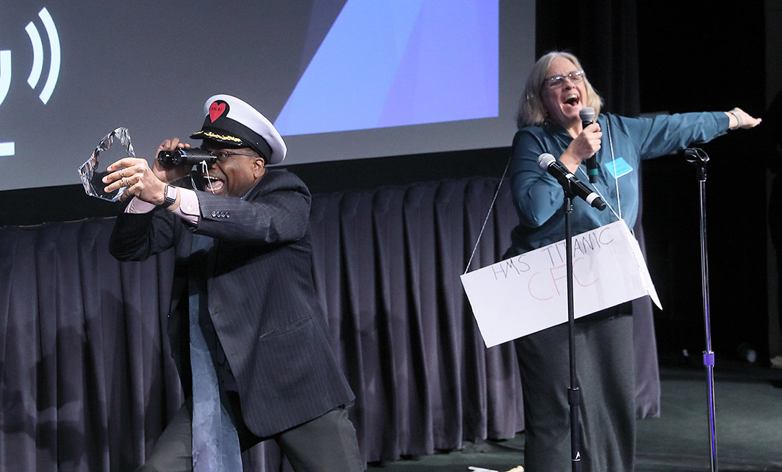Gibbons wearing captain's hat peers through binoculars and holds up a glass paperweight as Dunbar sings