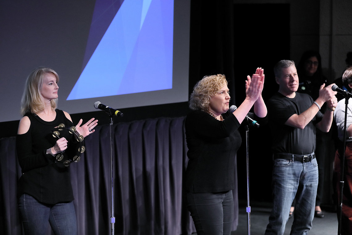 On stage, one woman plays tambourine, another claps, beside a man clapping.