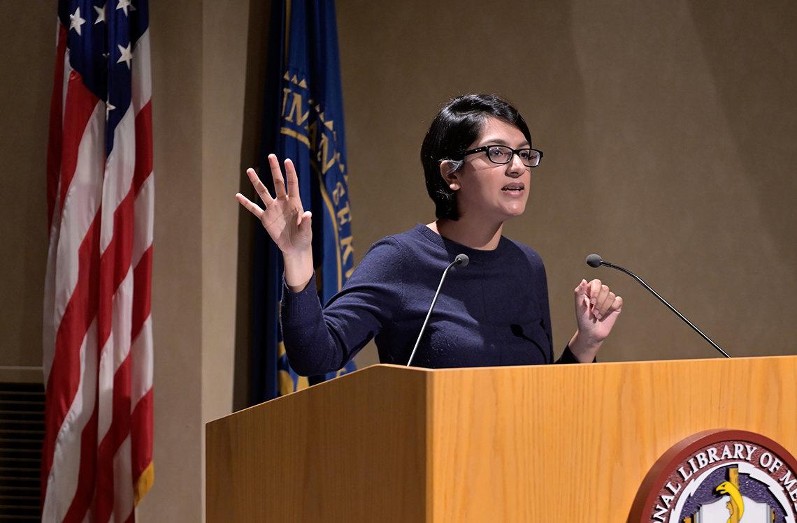 Saini speaks at podium