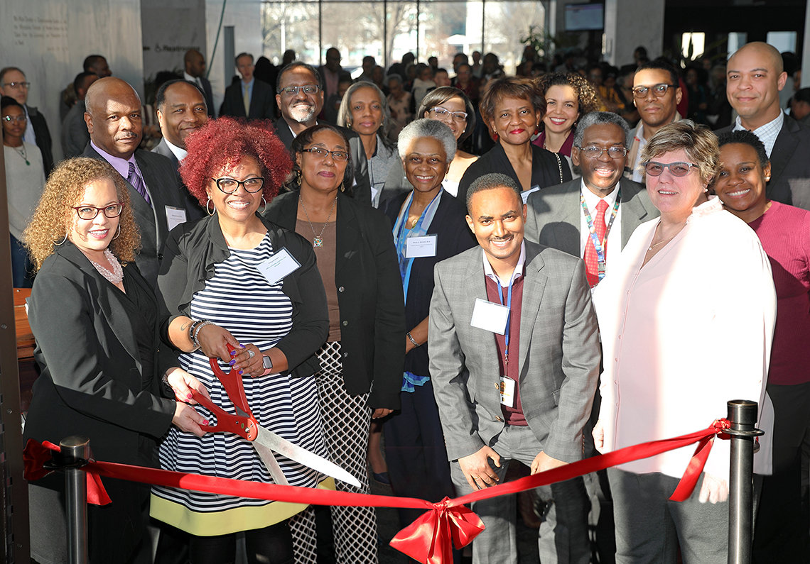 A smiling group of NIH'ers hold big scissors to cut the red ribbon marking the exhibit's opening.