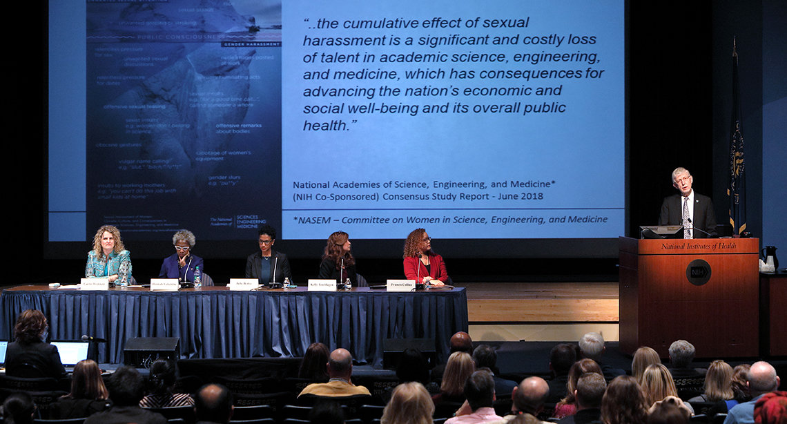 Dr. Collins speaks from podium with panelists seated nearby in front of slide that warns of the cumulative, costly effects of sexual harassment.