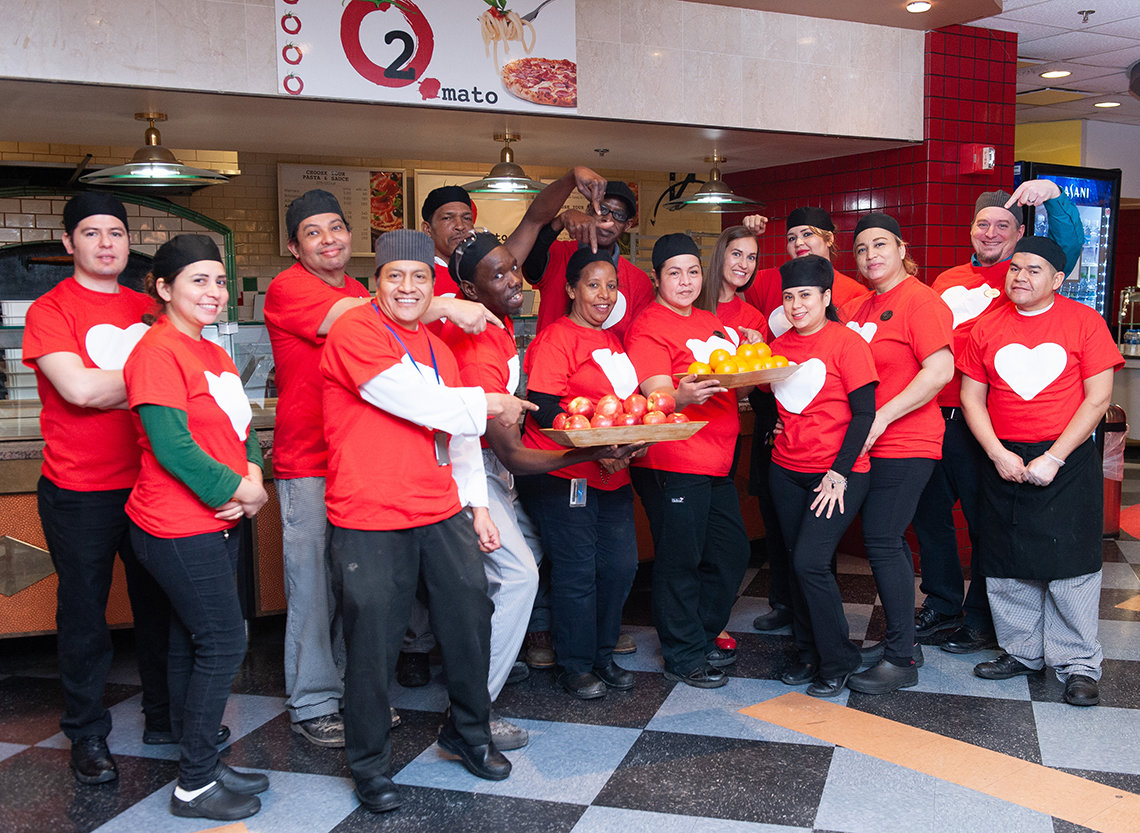 The smiling cafeteria staff from Bldg. 10 hold out trays of fruit