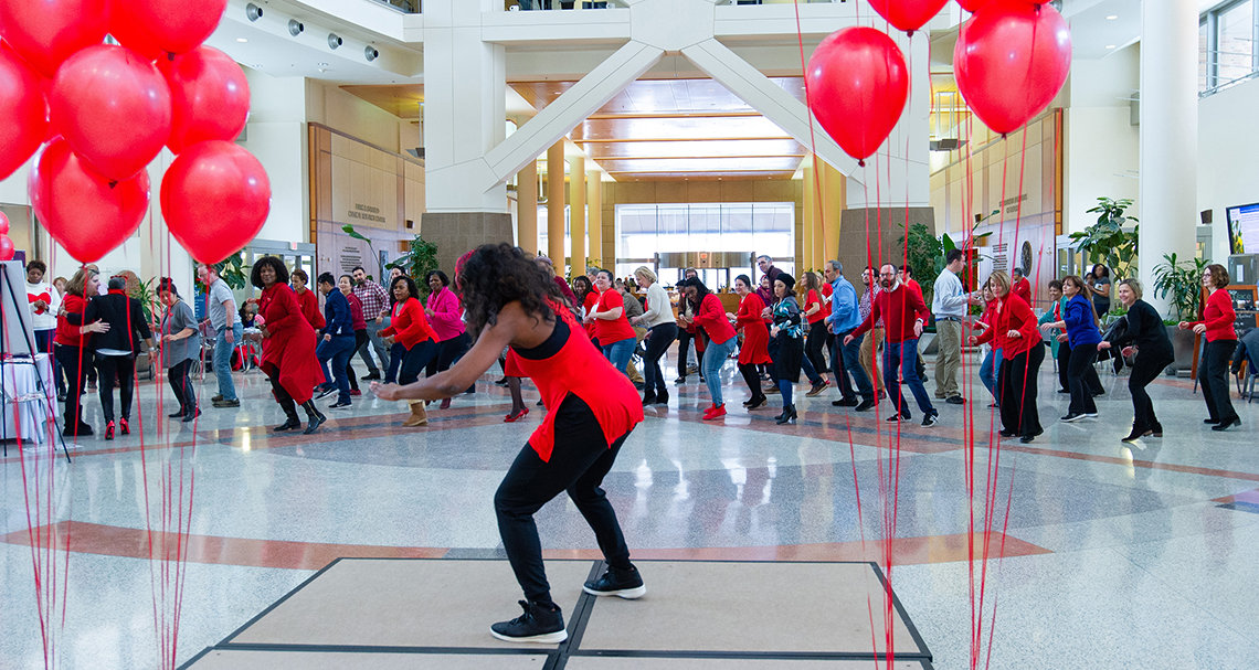 Fitness instructor leads a large group of NIH'ers in dance in Clinical Center atrium beneath red balloons.