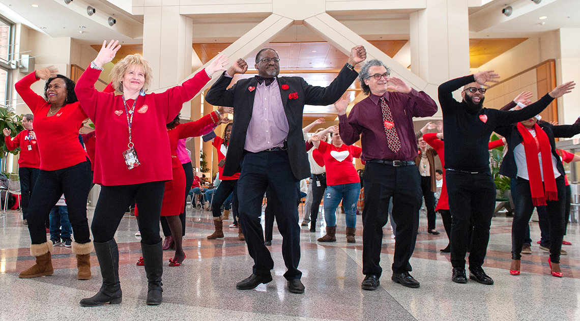 NHLBI and NIMHD directors and colleagues wave arms high in dance in Clinical Center's atrium.