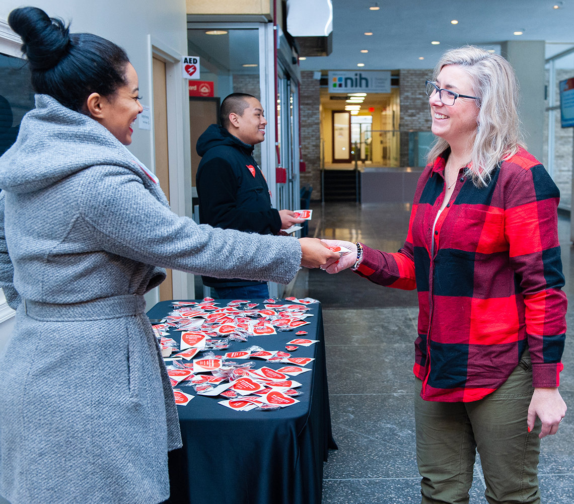 An NIH'er, beside a table of red heart pins, rewards a red shirt-wearing colleague with a pin in the Bldg. 31 lobby.