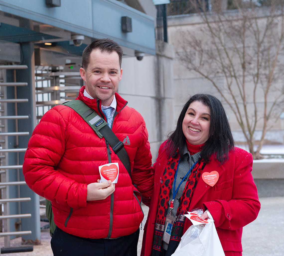 Two smiling NIH'ers in red jackets stand outside Metro station entrance eager to distribute heart stickers.